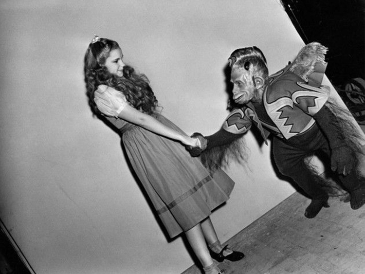 Dorothy (Judy Garland) and a Flying Monkey share a hand shake between scenes.