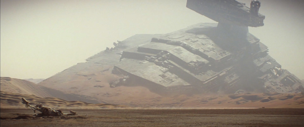 """That's nomountain, it's a spaceship. AnImperial Star Destroyer to be exact. In the foreground a downed X-Wing fighter. Both victims of the """"Battle ofJakku"""" which we will see in the upcoming game  Star Wars: Battlefront (BTW -  New trailer ). The X-Wing is one from the classic trilogy as the split wings engine is a full circle."""