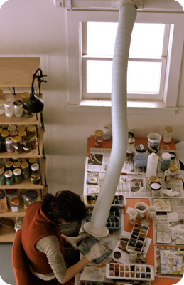 Rosario at the painting table, working under the fume hood