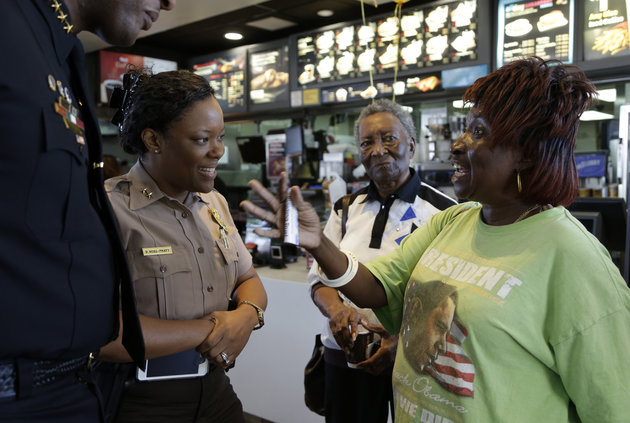 Dorothy Smith, right, talks with Miami-Dade county police officer Delma Noel-Pratt, left, during a Coffee with a Cop event at a local McDonald's on April 27, 2016, in Miami Gardens, Florida.  LYNNE SLADKY/AP