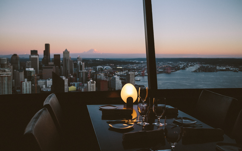Sitting in the Sky City Restaurant at the top of the Space Needle, with a view of Seattle and Mount Rainier in the distance