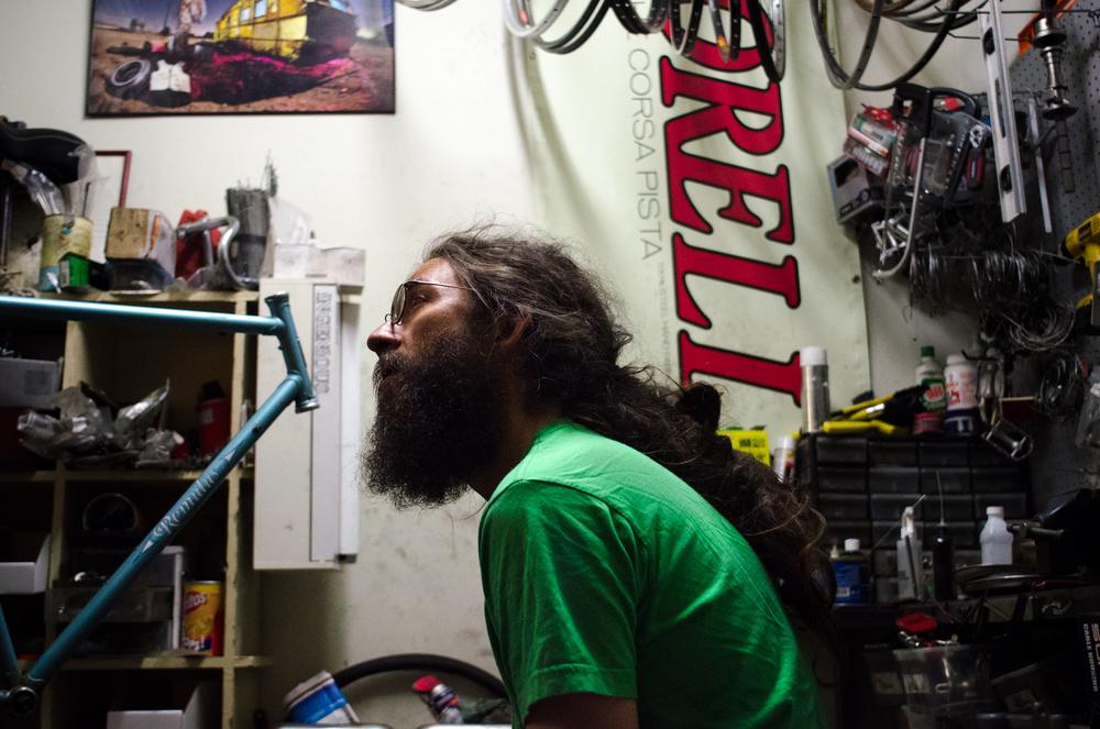 Seamus O'Neill, a local bike shop owner, listens to a customer's repair request. San Diego, 2013
