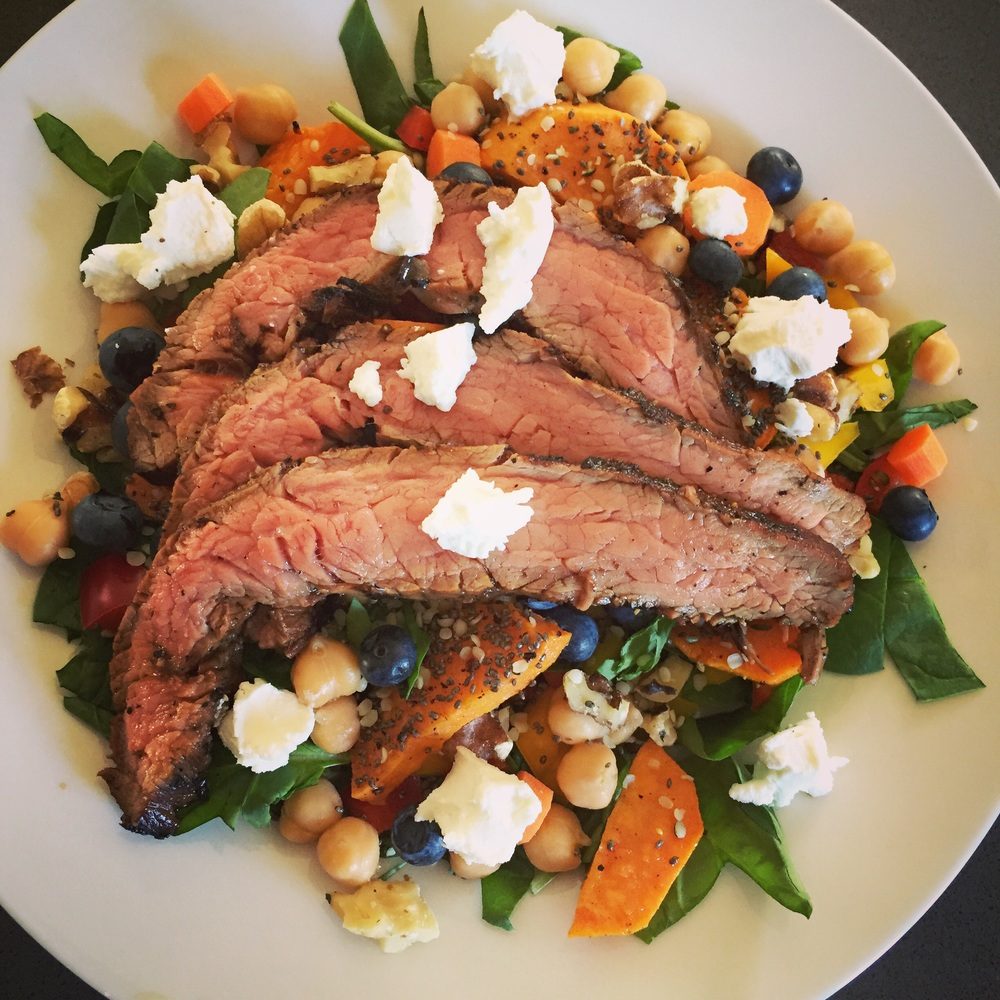 Barbecued flank steak on top of spinach, bell peppers, carrots, roasted sweet potatoes, blueberries, chickpeas, chia seeds, walnuts, hemp hearts, and goat cheese. Summer.