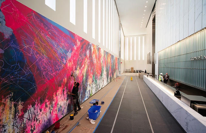 "This Nov. 7, 2014 photo provided by artist Jose Parla shows him painting one of his pieces in the lobby of the new 1 World Trade Center building in New York. Parla is known for his vibrant multi-layered and textured large-scale paintings, and this ""ONE: Union of the Senses"" is the largest of the works which decorate the lobby, which faces the Sept. 11 memorial fountains and museum. (AP Photo/Rey Parla)"