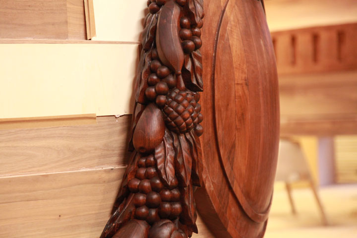 Detail of hand carved walnut swag and shield before gilding.