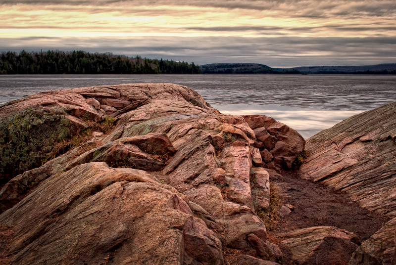 Winter ice melting over a lake, with a large rock look out. Algonquin park late March