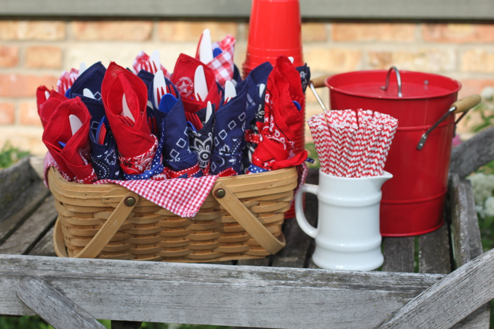 Wrap silverware in bandanas and finish with grosgrain ribbon for a casual backyard BBQ. The red and white chevron straws were a must! #TheCharmStudio