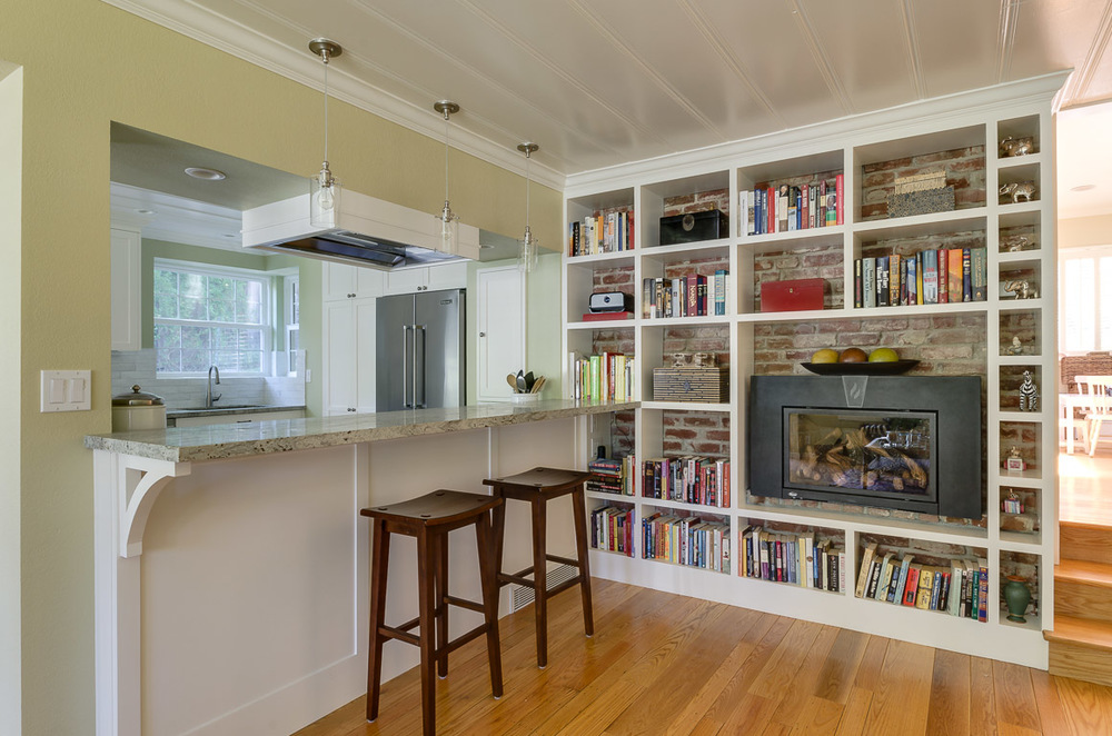 to a custom bookcase with an eating bar open to the kitchen.