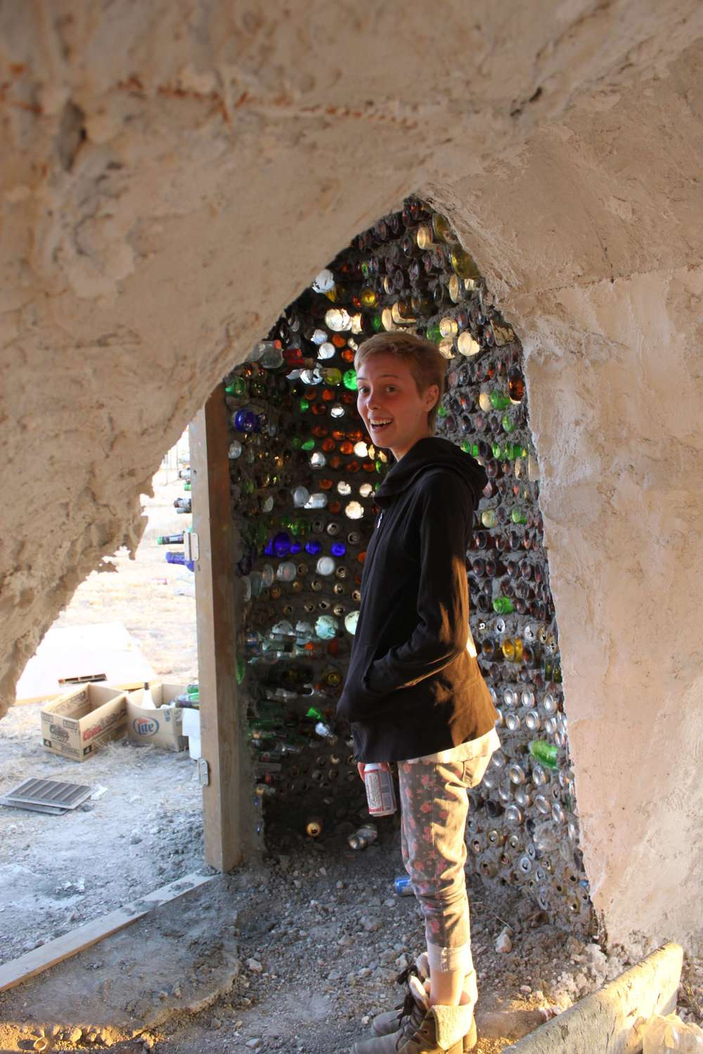 Angie in a castle ofold beer cans and bottles.
