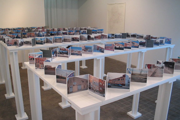 Monuments of toxicity: Getting to Know the Neighbors (2004), the first iteration of a local project that spans more than ten years, noting toxic sites in Williamsburg . Handmade accordion book of 396 hand-labeled photographs, on wood stand; dimensions variable