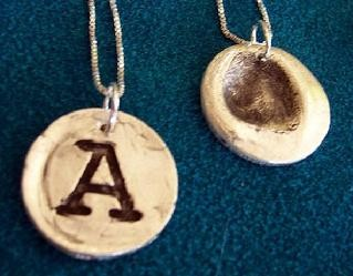 Front and back of a handmade, personalized silver necklace.