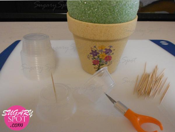 2.-  Haz una pequeña perforación en el centro del fondo del vaso de plástico, lo suficiente para que el palillo entre y quede a presión.