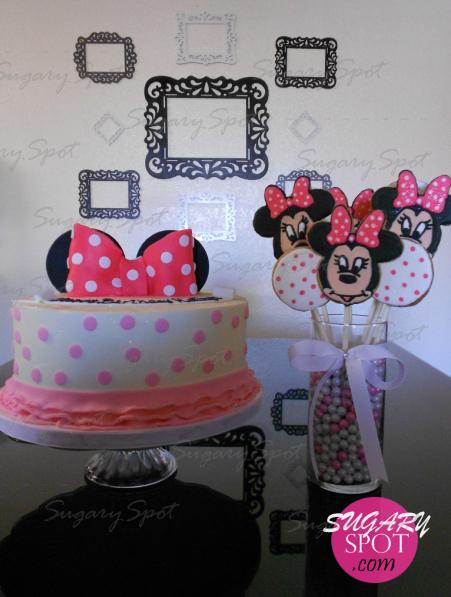 Pastel de Minnie Mouse y arreglo de galletas decoradas, en vase de cristal llena de bolitas de chocolate aperladas.