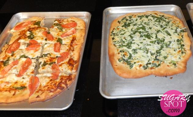 Izquierda: Pizza con salsa pesto como base, mezcla de queso mozzarella y queso ricotta, trozos de pechuga de pollo, gajos de jitomate y hojas de albahaca fresca.   Derecha: Pizza barnizada con aceite de ajo, con mezcla de quesos mozzarella y ricotta, seguida por una capa de espinacas frescas y mas queso mozzarella espolvoreado arriba.