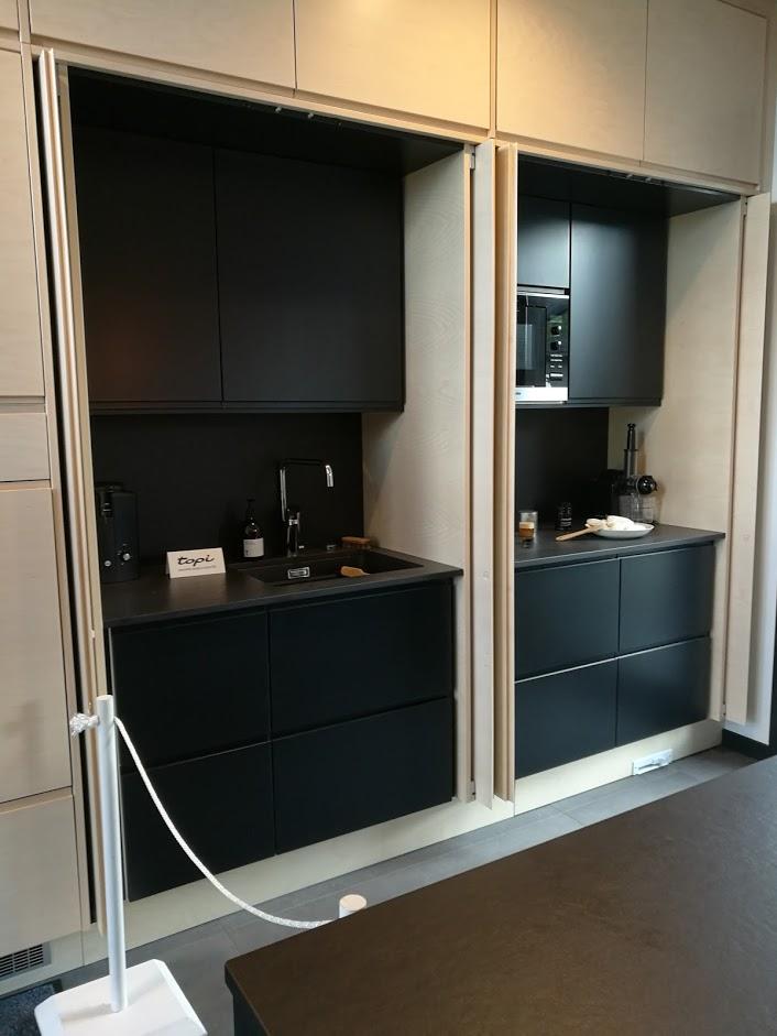 Upea musta keittiö, jossa sivuille liukuvien ovien taakse on kätketty eri keittiöyksiköt.