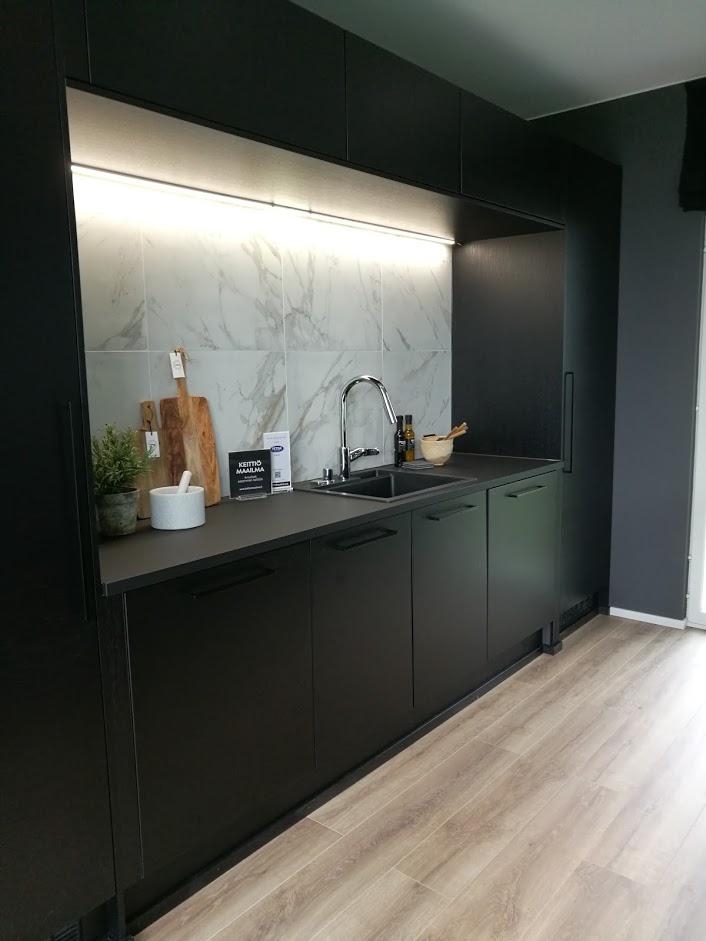Musta keittiö ja kauniit marmoriset laatat välitilassa.