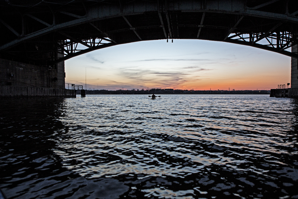 Sunset on the harbor through the archway of a bridge.