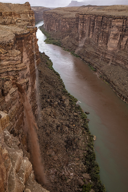 Waterfalls of mud falling down the canyon walls.