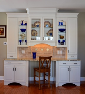 This hutch serves as a display cabinet, electronics storage and charging station, desk and file cabinet.  It was built inexpensively from stock cabinetry and finished to look like a built in.