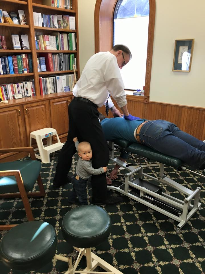 Dr. Sevlie adjusting his son with his one year old grandson helping out.