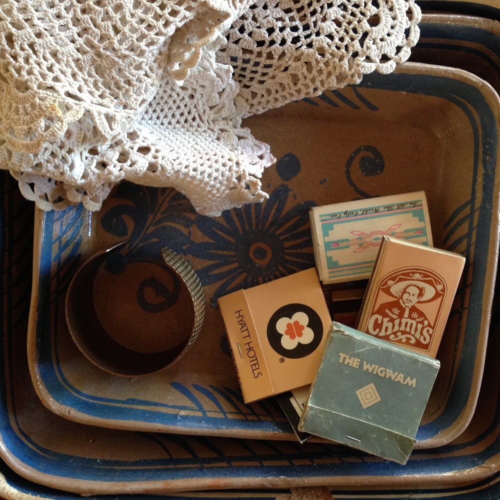Three 1940's Mexican baking dishes, a brass cuff bracelet, 2 doilies, and an assortment of vintage southwestern matchbooks.