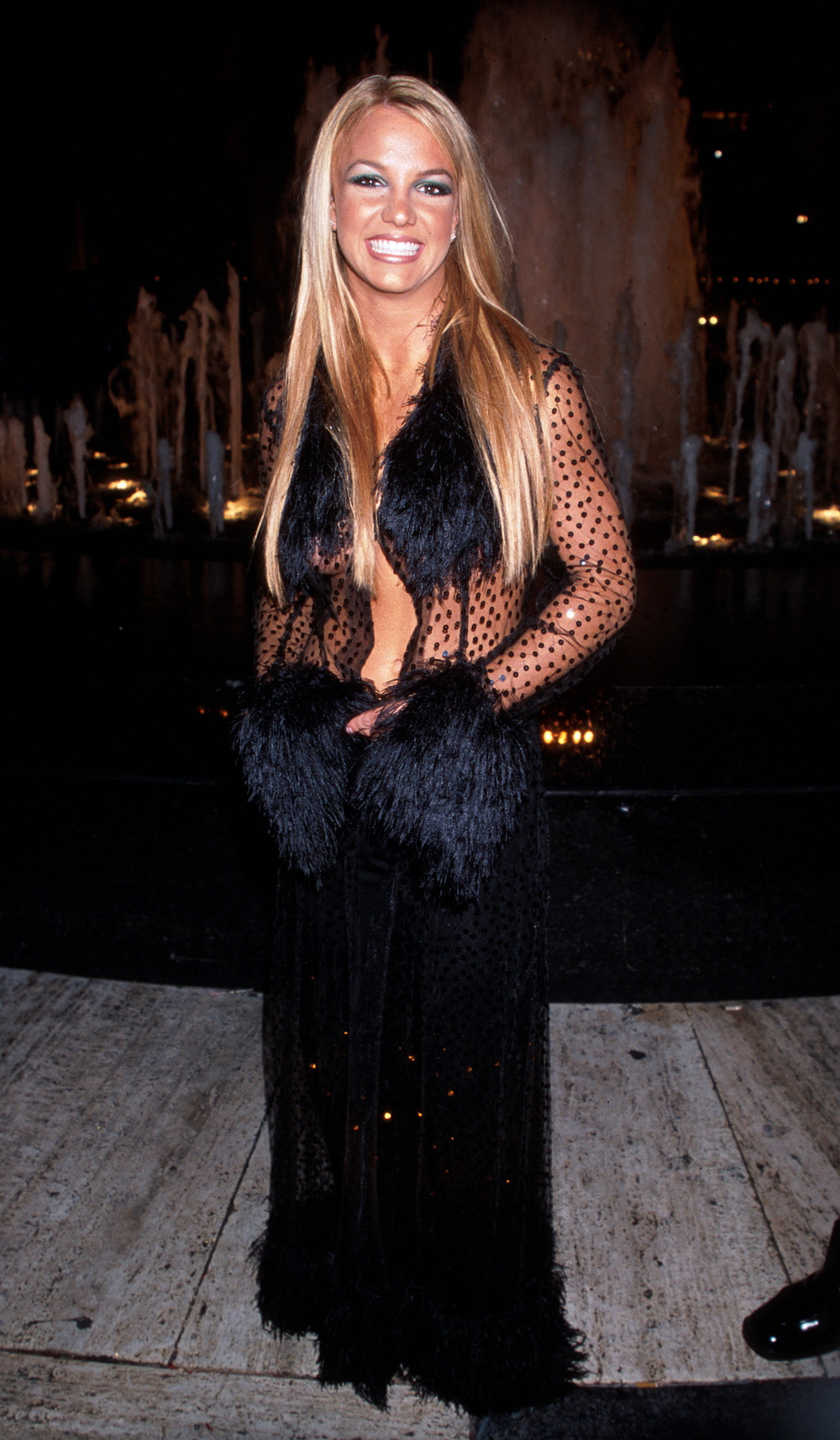 1999 : In a Risque sheer fur-lined coat and a long black skirt.