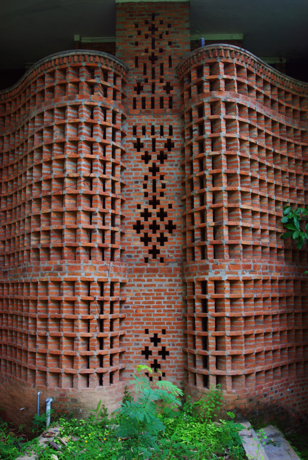 Women's Dormitory at the Centre for Development Studies, located in Ulloor, Trivandrum, completed in 1971 This building features some of Baker's most vitruosic brick work.  Two curved jali  walls fan outward from a central spine, creating a breezy, shaded shared corridor space.  The monolithic walls rise up two and a half stories, and end in a handrail on the third storey balcony.  Private rooms are located at the back of the building, shielded from the public walkway.