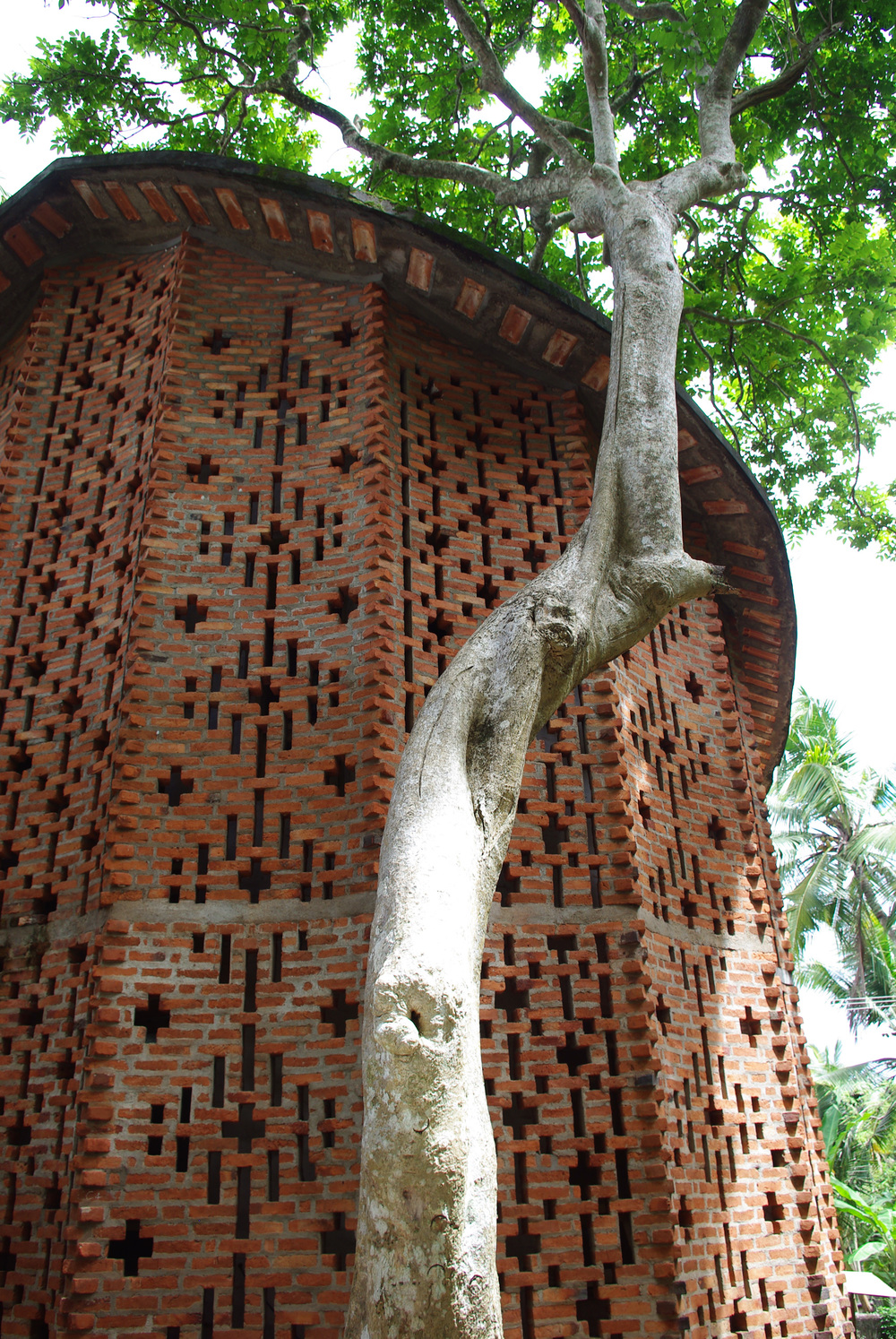 Computer Centre at the Centre for Development Studies, located in Ulloor, Trivandrum, completed in 1990 Added at a later date than the original campus buildings, the Computer Centre features a unique double-skin brick wall.  The exterior enclosure is made of a series of short curved segments, adding structural stability to the thin wall.  The internal enclosure was designed to accomodate the requirements of the computer labs.  The space between the two boundaries houses offices and storage areas.  The two walls regulate sunlight, eliminating glare while allowing natural light to penetrate the interior.