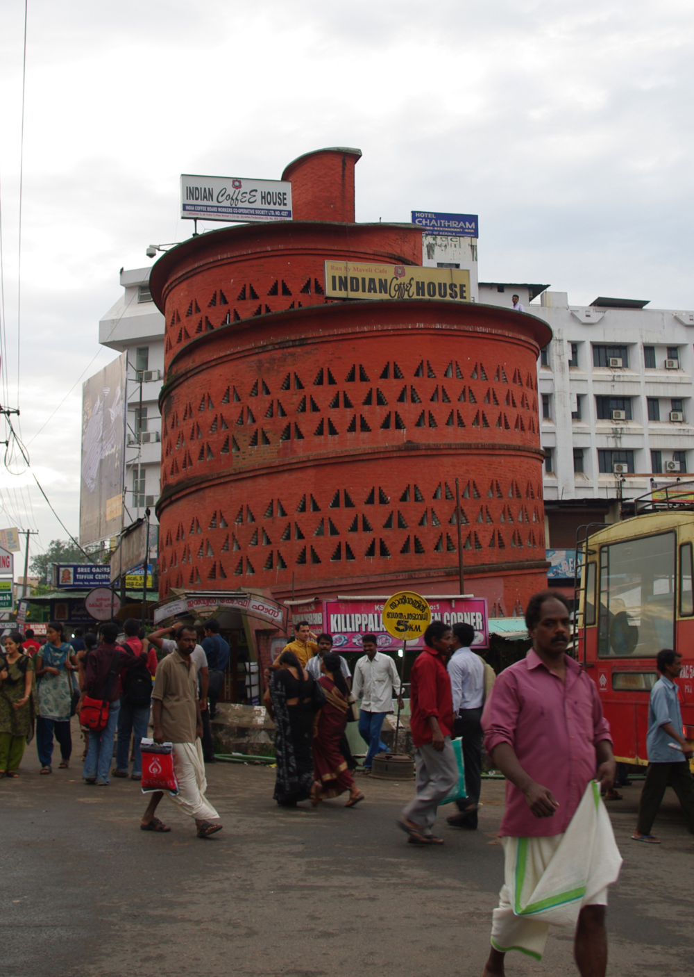 Indian Coffee House, located in Thampanoor, Trivandrum, completed in 1974   The downtown branch of the Indian Coffee House is among the most iconic buildings in Trivandrum.  Sited opposite the train station and adjacent to the bus depot, the structure serves as an arresting symbol of the city, its red paint glowing during the day and its lantern-like perforations emitting light at night.  The cafe's seating is arrayed along a continuously sloping spiral path.  At the center of the spiral is a stacked series of bathrooms, ventilated through a central chimney.  Inside, the spiral terminates in the manager's office, which opens onto a roof that affords generous views of the capital.