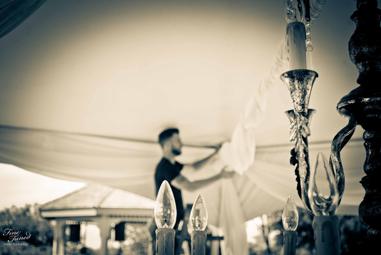 Adam sets up the lights he made, for his wedding, hours before the rings go on.