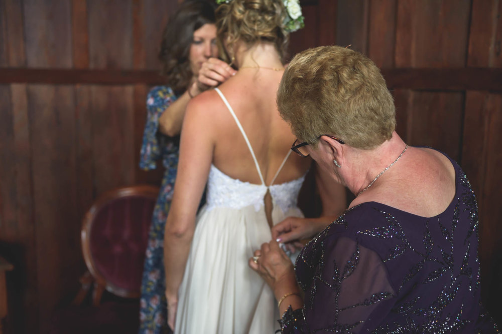 Bridesmaid and mother help with bride with wedding dress.