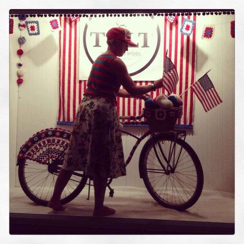 photo by Anna Dianich of Tolt Yarn & Wool me working on the finishing touches of our yarn bombed vintage Schwinn for a 4th of July Yarn shop window display.
