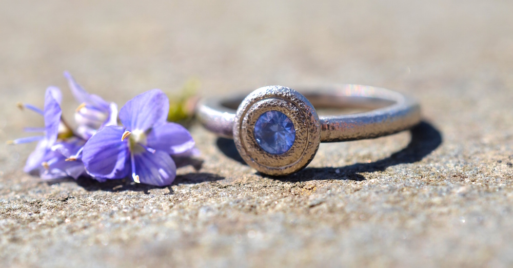 A sapphire set in a rustic white gold, hammered finish ring