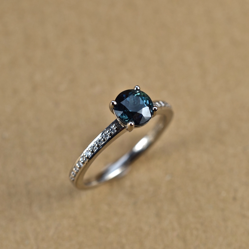 The sapphire looks a darker teal colour in different lighting