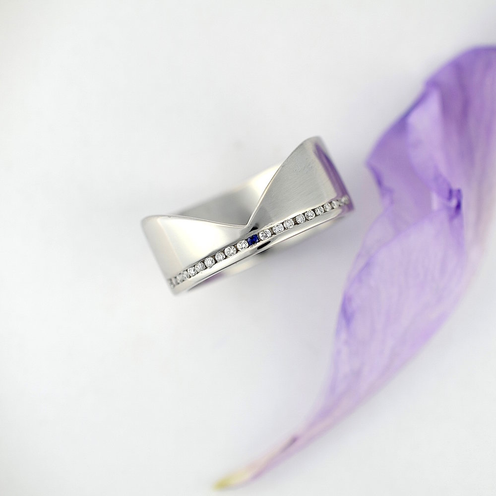 Platinum wedding band with pave set diamonds & a sapphire