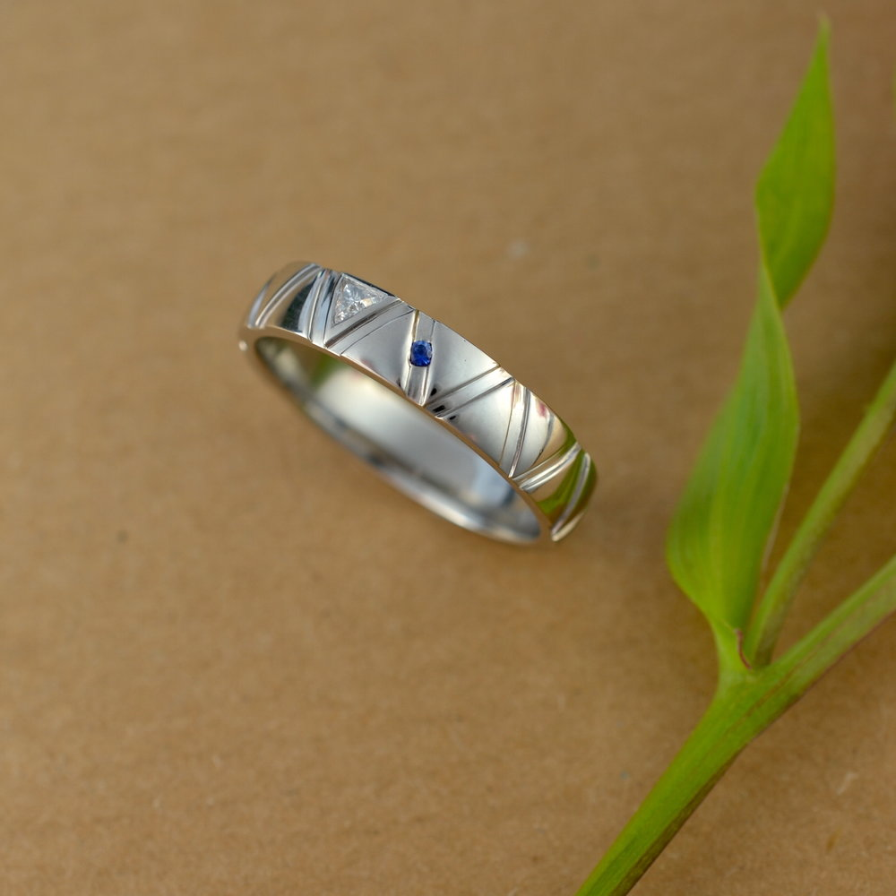 Palladium wedding ring with trillion cut diamond and a sapphire
