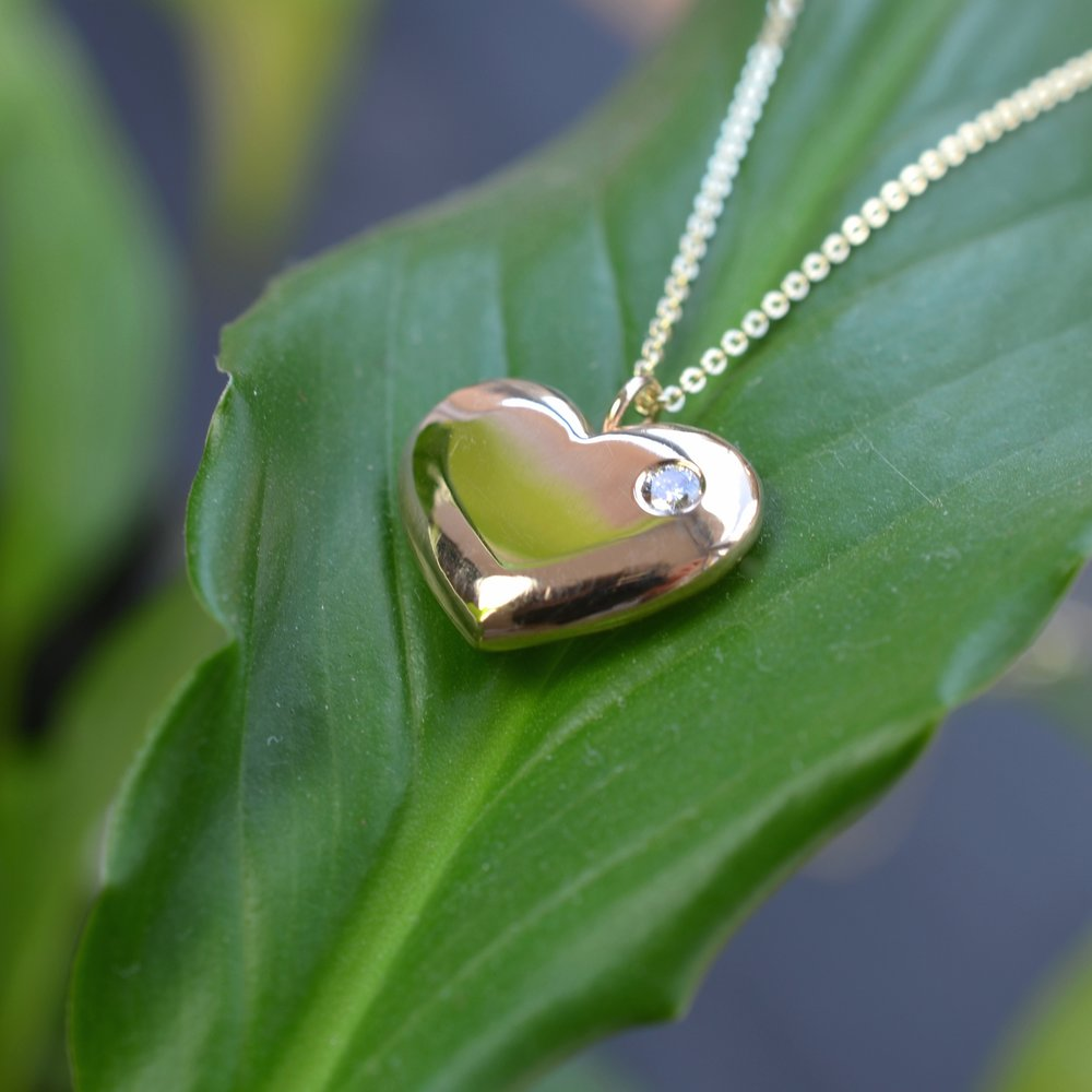 A new gold heart pendant created in gold from an old, treasured heirloom, set with one small stone