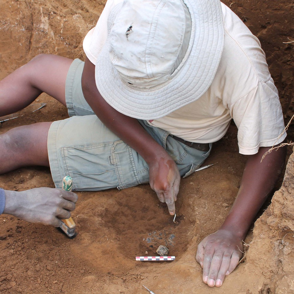 Small and intentionally dug hole that contained about 550 artifacts. The people at the site (~94,000 years ago) appeared to have dug a hole and swept up their mess - small sharp shards of glass from resharpening and shaping various types of tools.