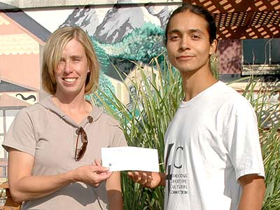 Kirstin Brown, friend and colleague of David Bucknam, presents Tomas Shash, right, with his scholarship check in Durango, Colorado