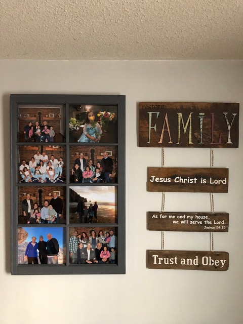 """I love this. An old window frame, repurposed . . . now hanging in our entryway. It brings a smile to my face each time we walk through the door and are greeted by these sweet smiles of our family. And the repurposed old flooring from CBS from which Paul's sister Beth salvaged the wood and stenciled our life mission statement. Joined by chain to """"FAMILY"""" —a plaque given to us by my sister Laura, we're reminded daily of eternal truths."""