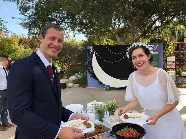 Brandon and Emma (Kelly) Zeek celebrating their wedding at the outdoor reception.
