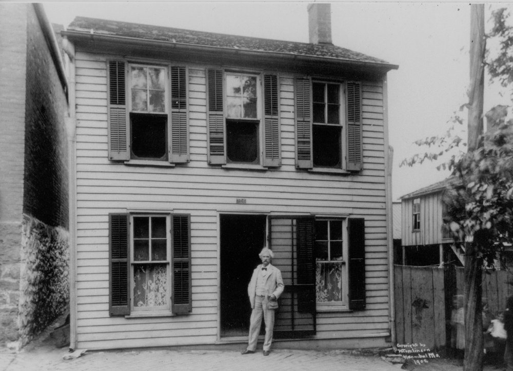 Mark Twain in front of his boyhood home during his last visit to Hannibal in 1902.       Photo copyright the Hannibal Convention and Visitors Bureau