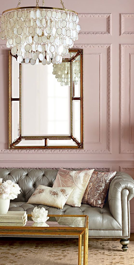 Image: DigsDigs   Doesn't this gorgeous silver grey leather Chesterton sofa just pop against those gorgeous pink walls? And the moulding? The Capiz shell chandelier? The gold coffee table? Wow!