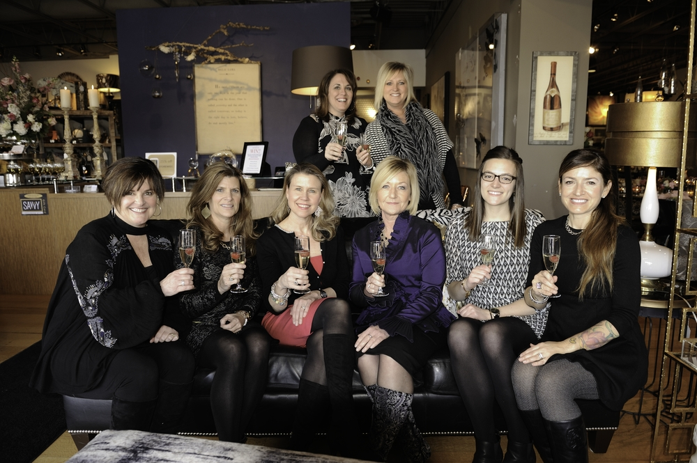 Toasting to our beautiful beginnings and our very bright future! Standing (L to R) Diane Fogerty, Principal and Owner, Becky Gale, Operations Manager; Seated (L to R) Kathleen Matthews, Interior Designer, Laurie Morris, Project Manager, Judy Uelk, Marketing Manager, Karen Smith, Interior Designer, Lindsey Jungk, Project Manager, Lisa Rapp, Visual Merchandiser and Buyer.