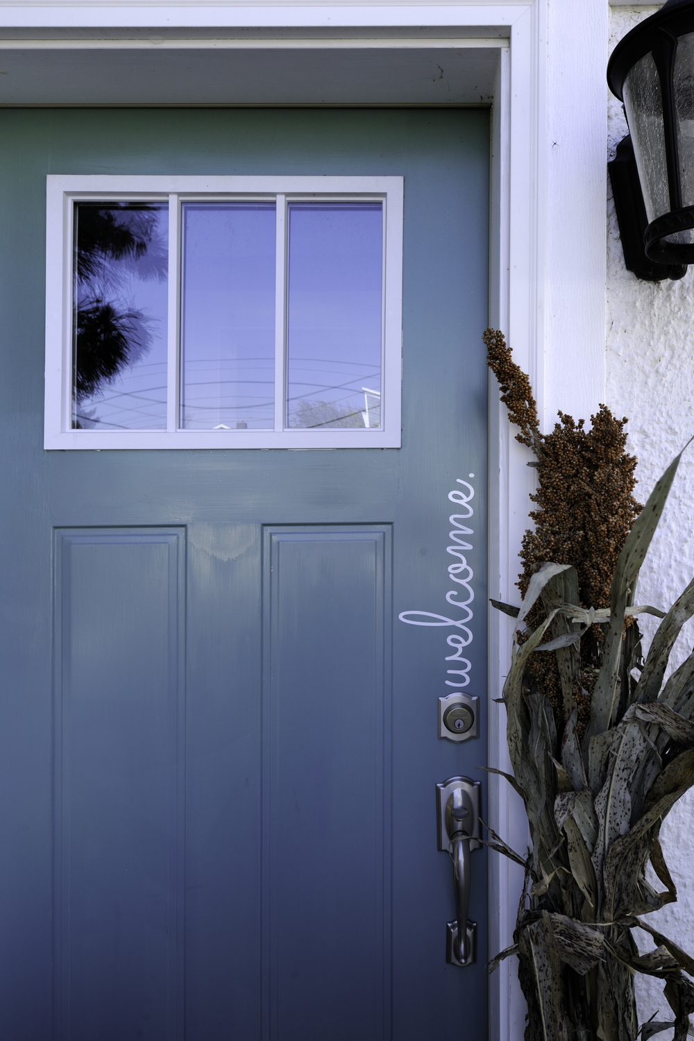 "Love this pretty blue door and the adorable ""welcome"" detail."
