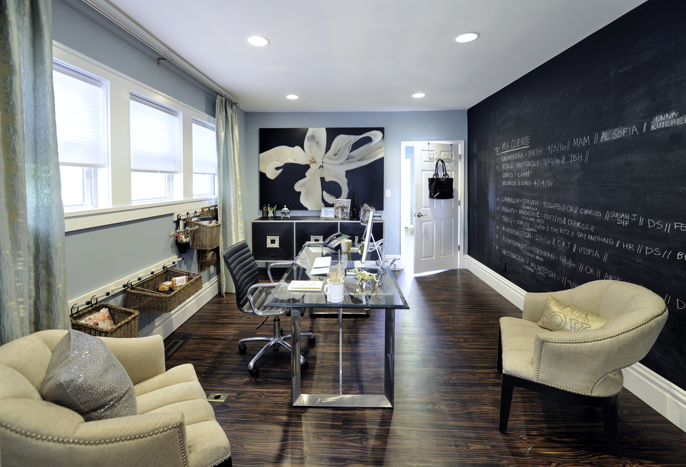 Kate's office is a study in how elements of a commercial space can overlap seamlessly to a residential application. Wouldn't this be an awesome home office?! As the owner and principal designer at this busy wedding planning company, Kate chose to cover an entire wall in front of her desk with chalkboard paint to help keep her organized and on task. A soft blue wraps the rest of the office in calm, and shimmering window panels in a similar hue enhance without distracting. Creamy upholstered chairs in a romantic, rounded silhouette and accented with brass nailhead trim are comfortable for clients and fit the style and feel of this office perfectly. A contemporary glass topped desk with chrome legs is a great foil for the otherwise softer elements in the room. Pops of black in the art deco inspired credenza and gorgeous oversized floral painting ground the space and add punch. And what about those baskets on the wall? What a great storage solution when a furniture piece would have been too much.
