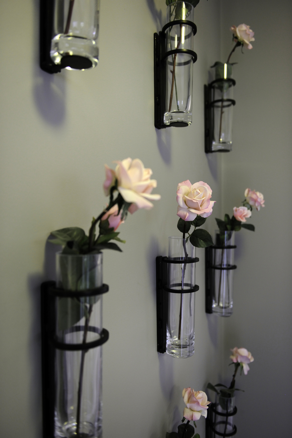 "Hanging wall vases offer a ""living"" art piece in a hallway."