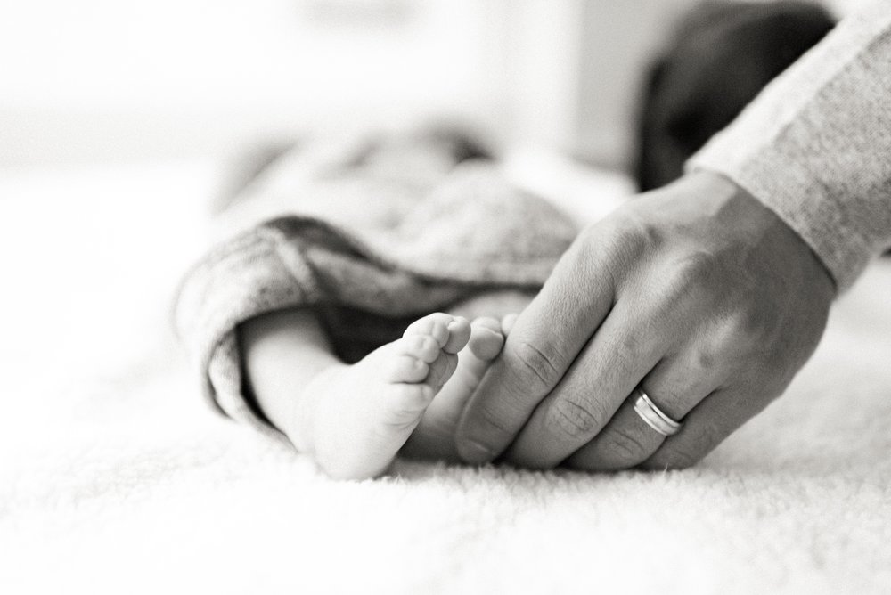 newborn baby feet with dad's hand and wedding ring