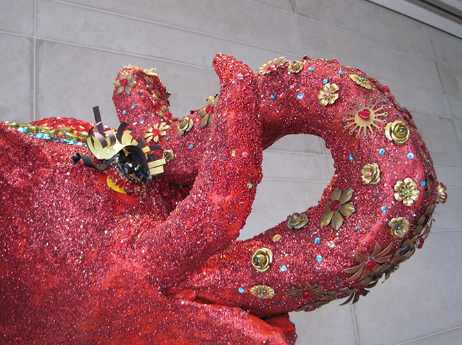 The decoupaged elephant head encrusted with jewels, glitter and brass fixings.