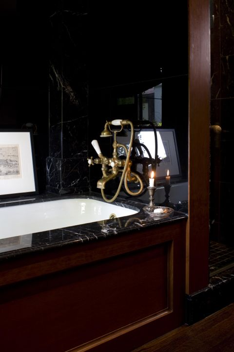 Old World glamour is brought to my bathroom with a black glass and marble tub, vintage brass faucets and cherrywood accents. (Casey Design/Planning Group Inc. - Photo by Ted Yarwood)